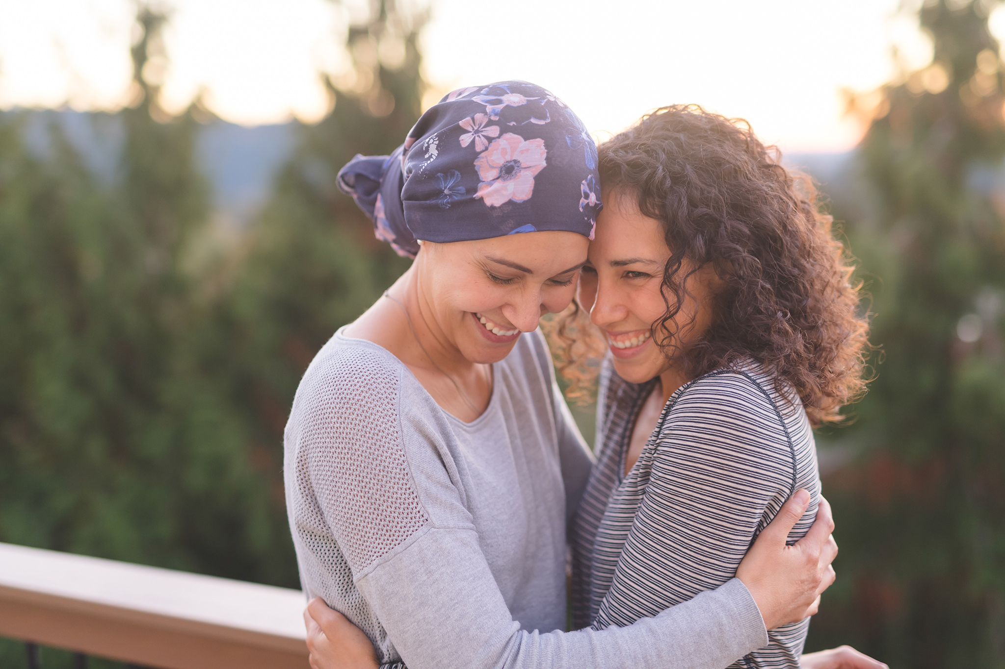 Woman cancer patient with scarf hugging another woman
